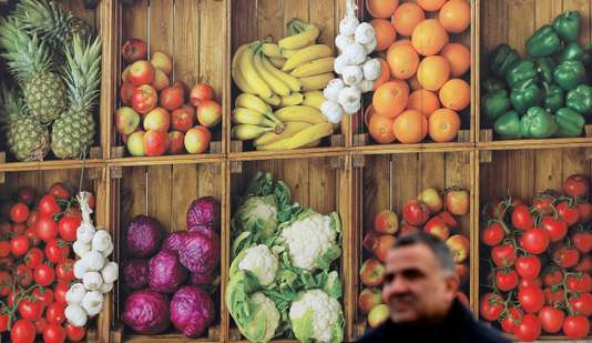 A man walks past a Nisa Grocers delivery lorry with fruit and vegetable livery in Wolverhampton